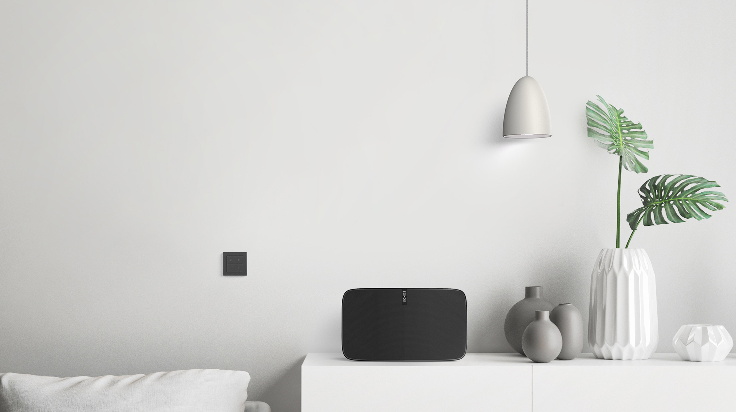 Nuimo Click Black on a stylish architectural white design. Next to it is a Sonos dark speaker and some green plants