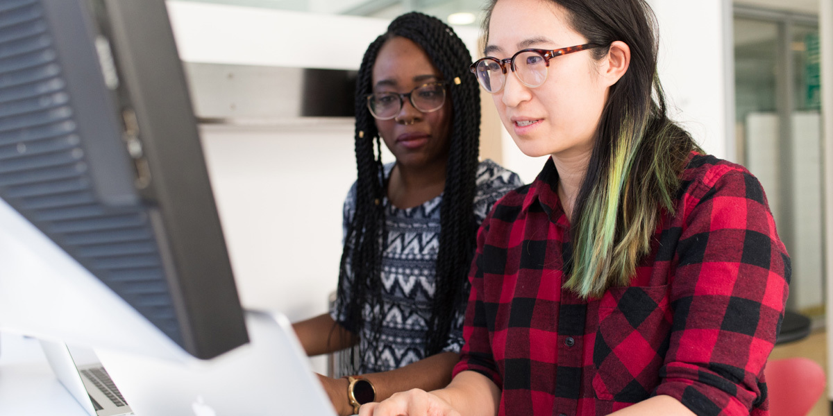 Two women digital designers sitting in front of the same laptop