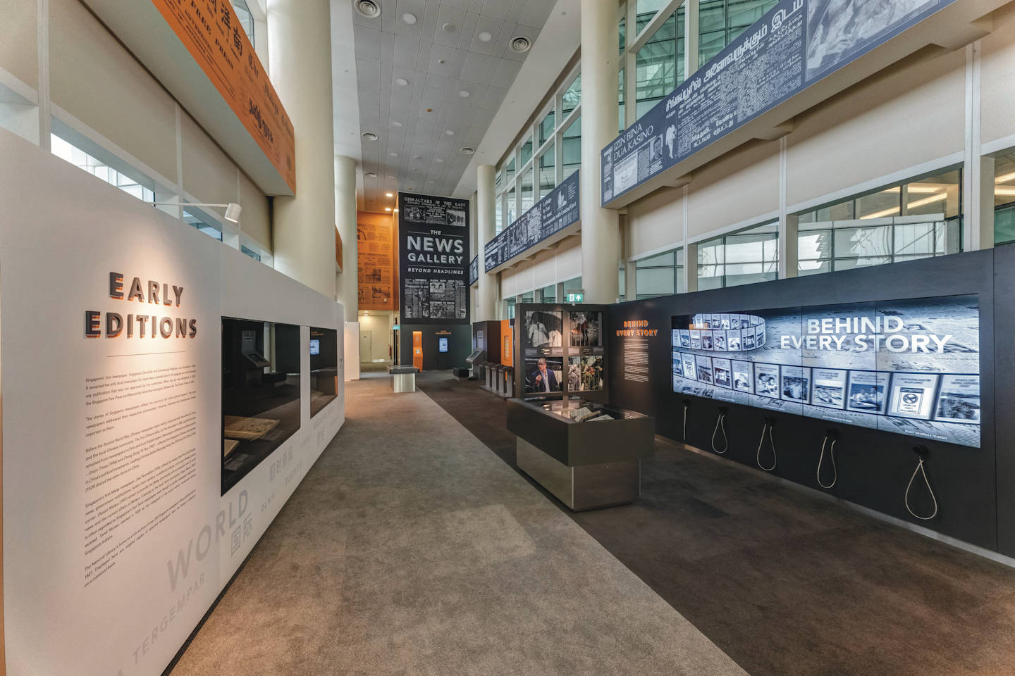 Photo of the News Gallery's introduction wall. Tall multimedia touchscreens next to it are featuring 'behind the scenes' information on news articles.