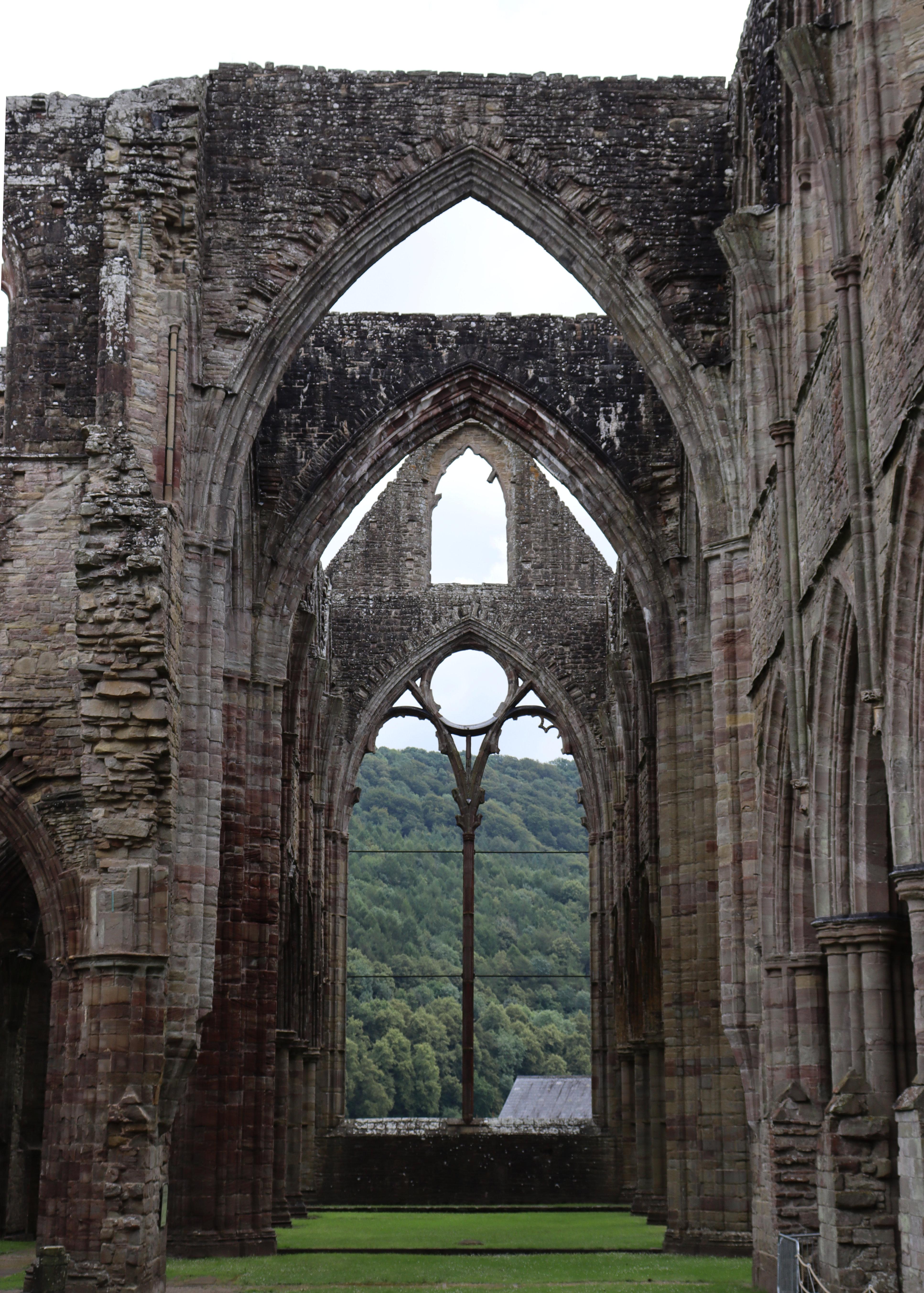 Archways aligning with windows inside Tintern Abbey.