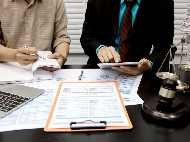 Zwei Personen sitzen an einem Tisch und beraten sich zu einem Dokument, auf dem Tisch steht eine Waage.