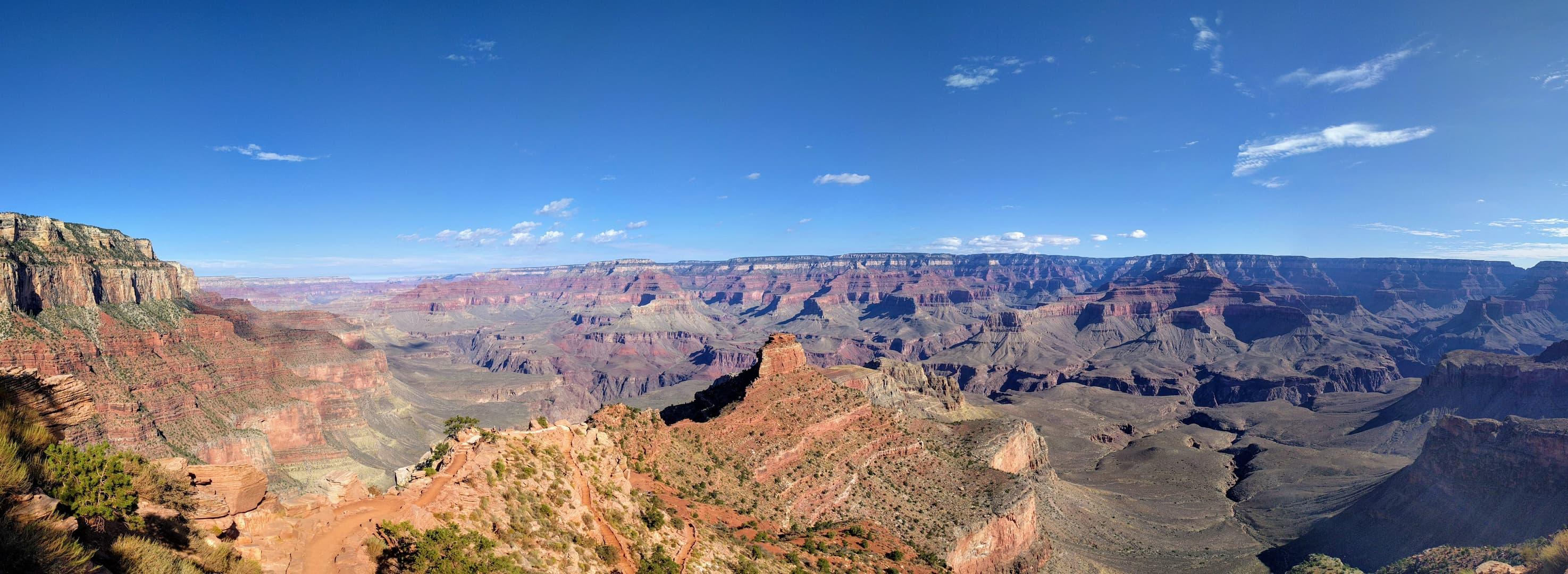 A mesa-like 'temple' near the end of a long ridge descending towards the floor of the Grand Canyon from the South Rim. Parts of the trail down to the floor of the Canyon can be seen in the foreground.