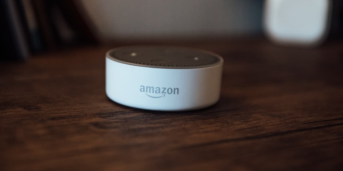 An Amazon Alexa device sitting on a wooden table