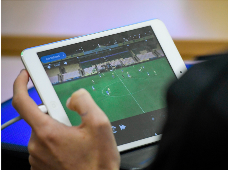Person viewing soccer match videos on a tablet