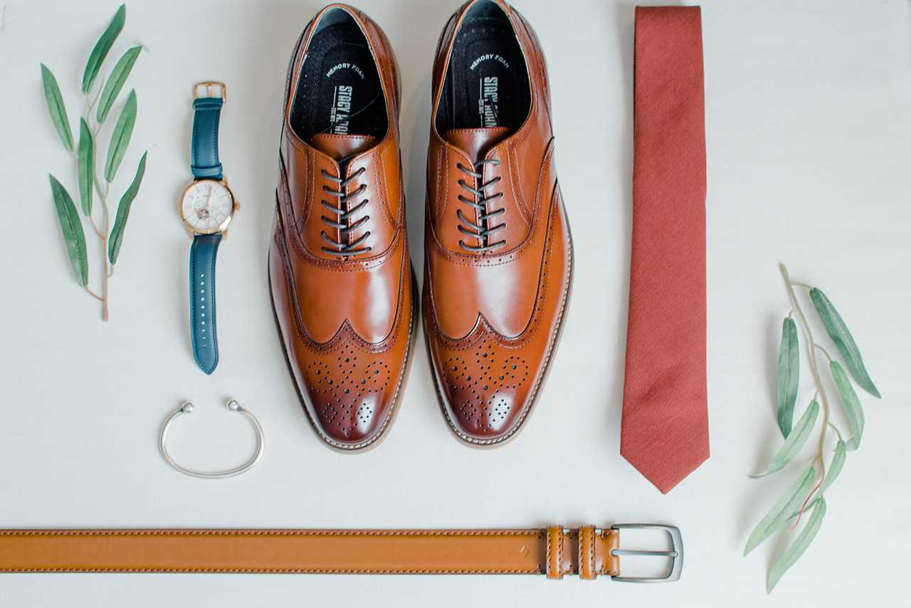 Shoes, a watch, a tie, and a wrist band against a slate white background