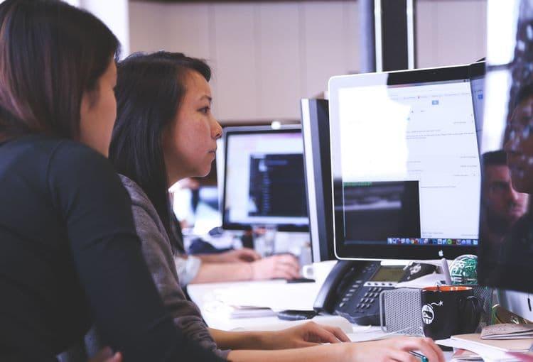Trainer vor Ort hilft Mitarbeiterin bei technischen Problemen