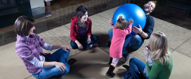 Family of five playing and sitting together on the floor | Family Therapy