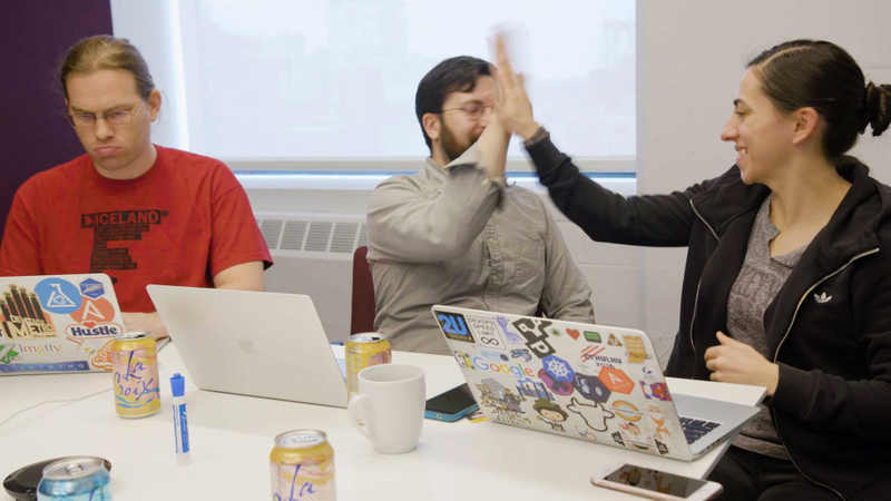 Colleagues high five each other next to laptops with lots of stickers on them