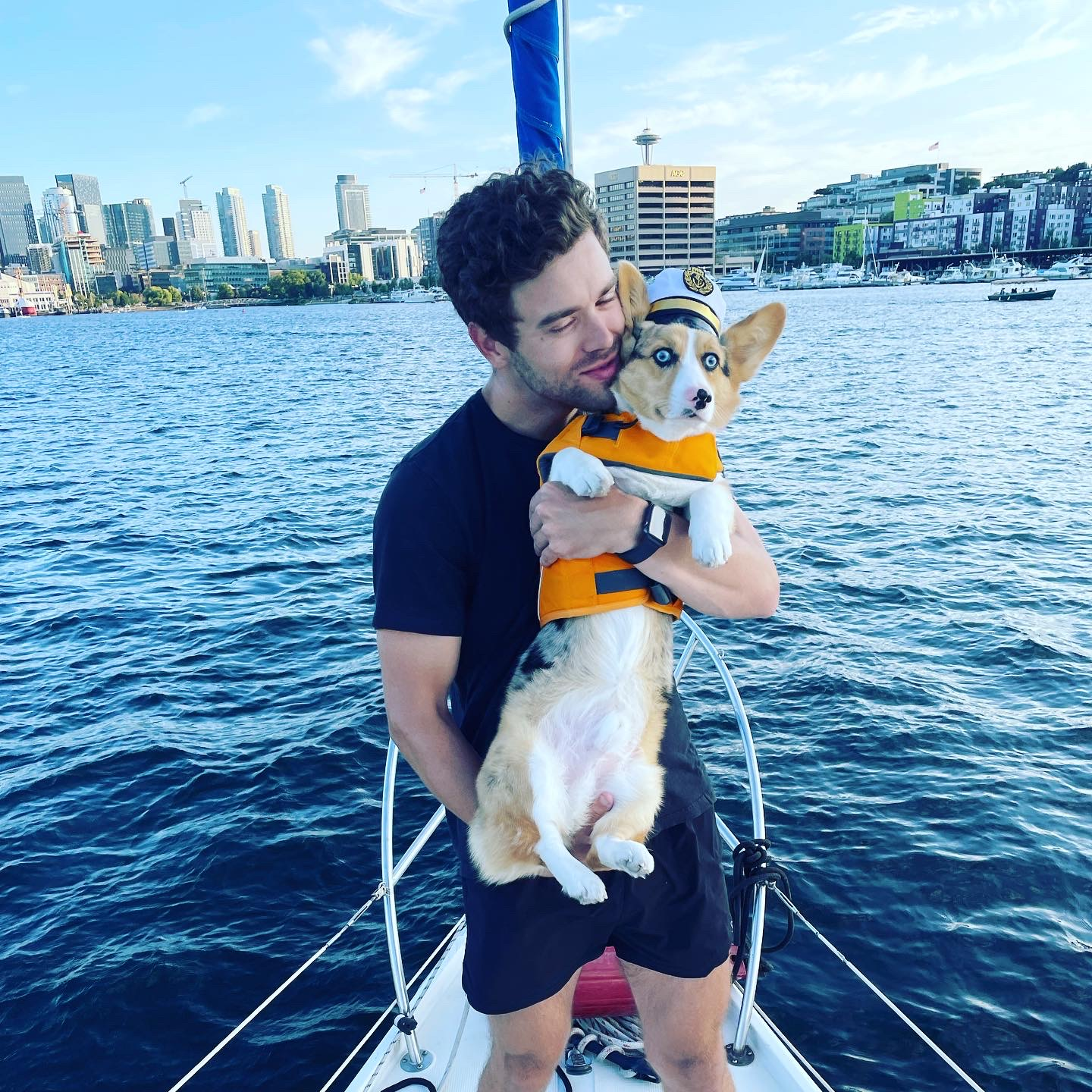 Gage holding a corgi on the bow of a sailboat