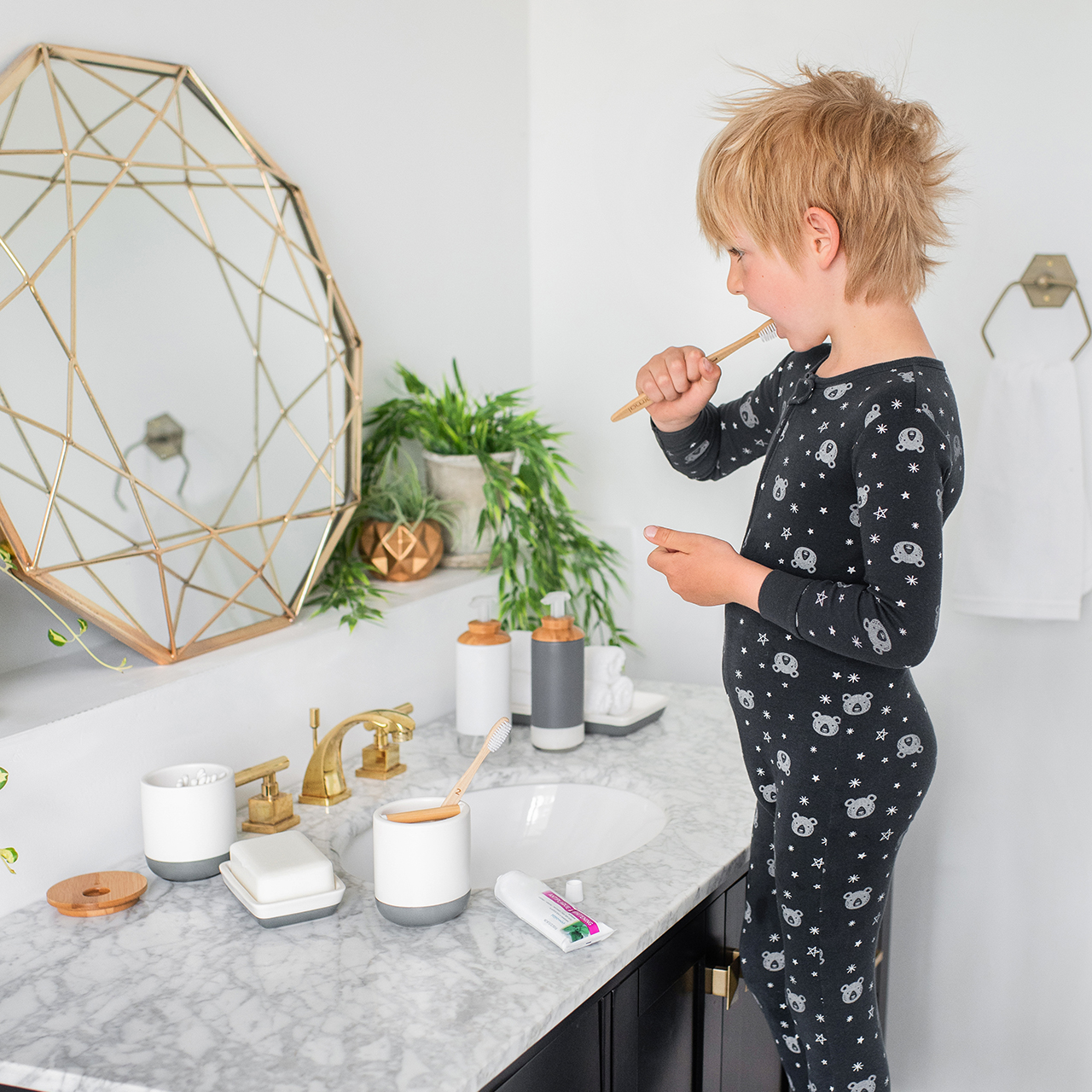 Young boy in pajamas stands on a stool and looks into a mirror while brushing his teeth