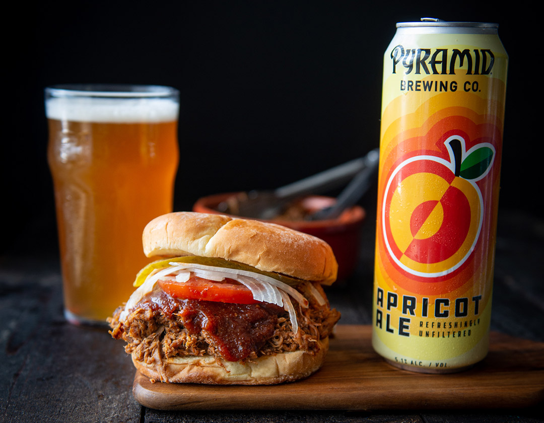 Pulled pork sandwhich on a cutting board next to a can of Apricot Ale