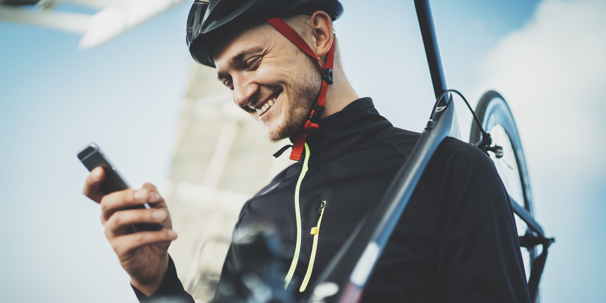 A person carrying a bike, looking at their phone and smiling