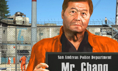 Grand Theft Auto character in orange jumper holds sign in front of prison