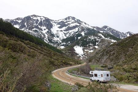 An RV driving along an empty mountain road, from MemoryCatcher of pixabay.