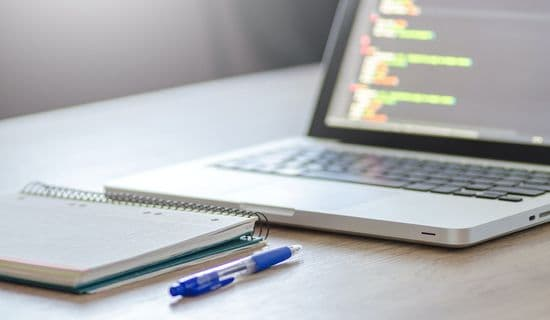 Laptop mit Block und Stift