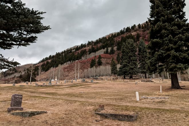 A mountain cemetary. The sky is cold and gray, but some of the bushes on the small rise behind the cemetary are a striking red color.