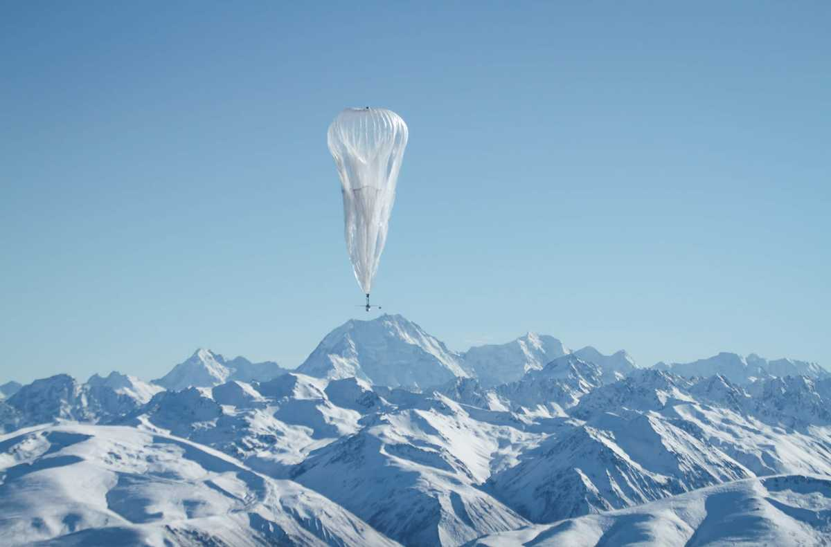 Weather Balloon flying above a snowy mountain range