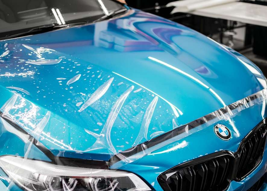 Paint protection film (PPF) being applied to bonnet/hood of blue BMW M2C