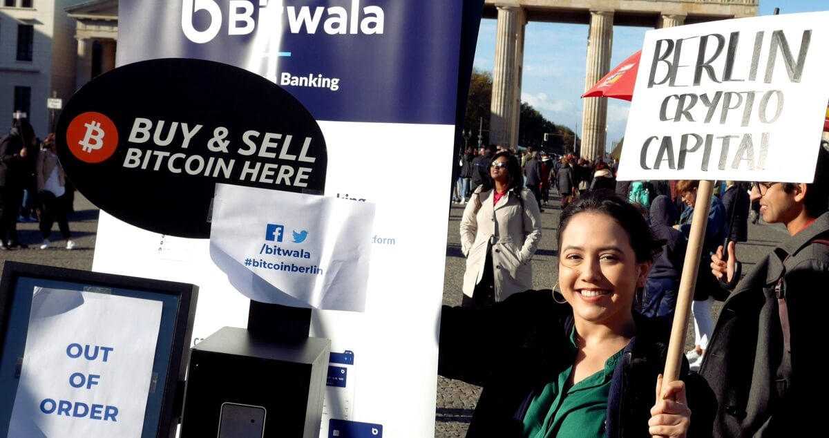 bitwala employee holding a bitcoin sign
