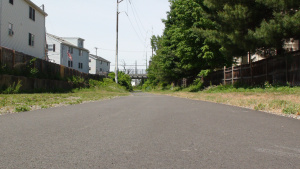 A picture of a paved bike path, with a neighborhood in the background, on a summer day.