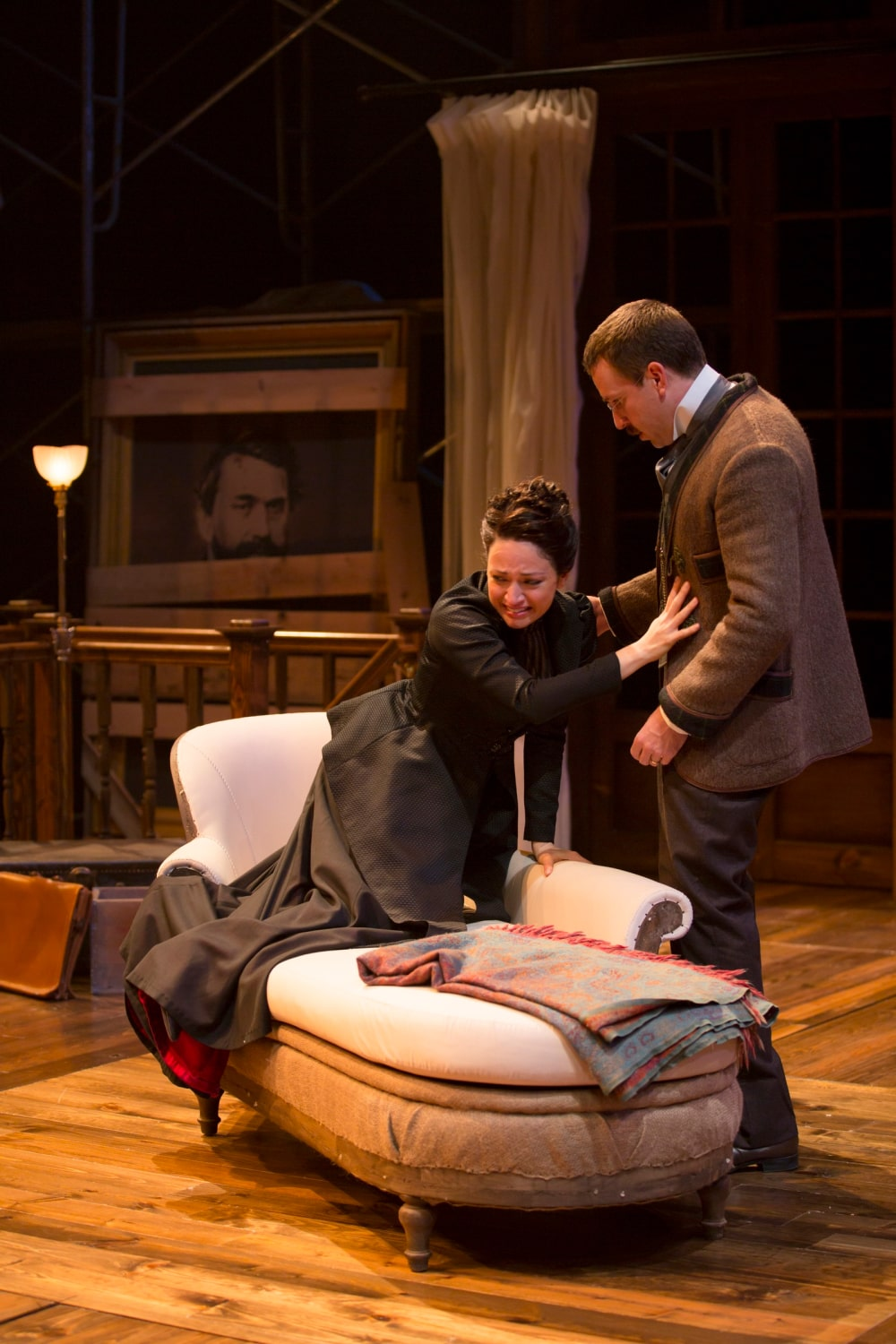 Distraught woman in black suit dress kneels on chaise reaching for spectacled man standing beside.