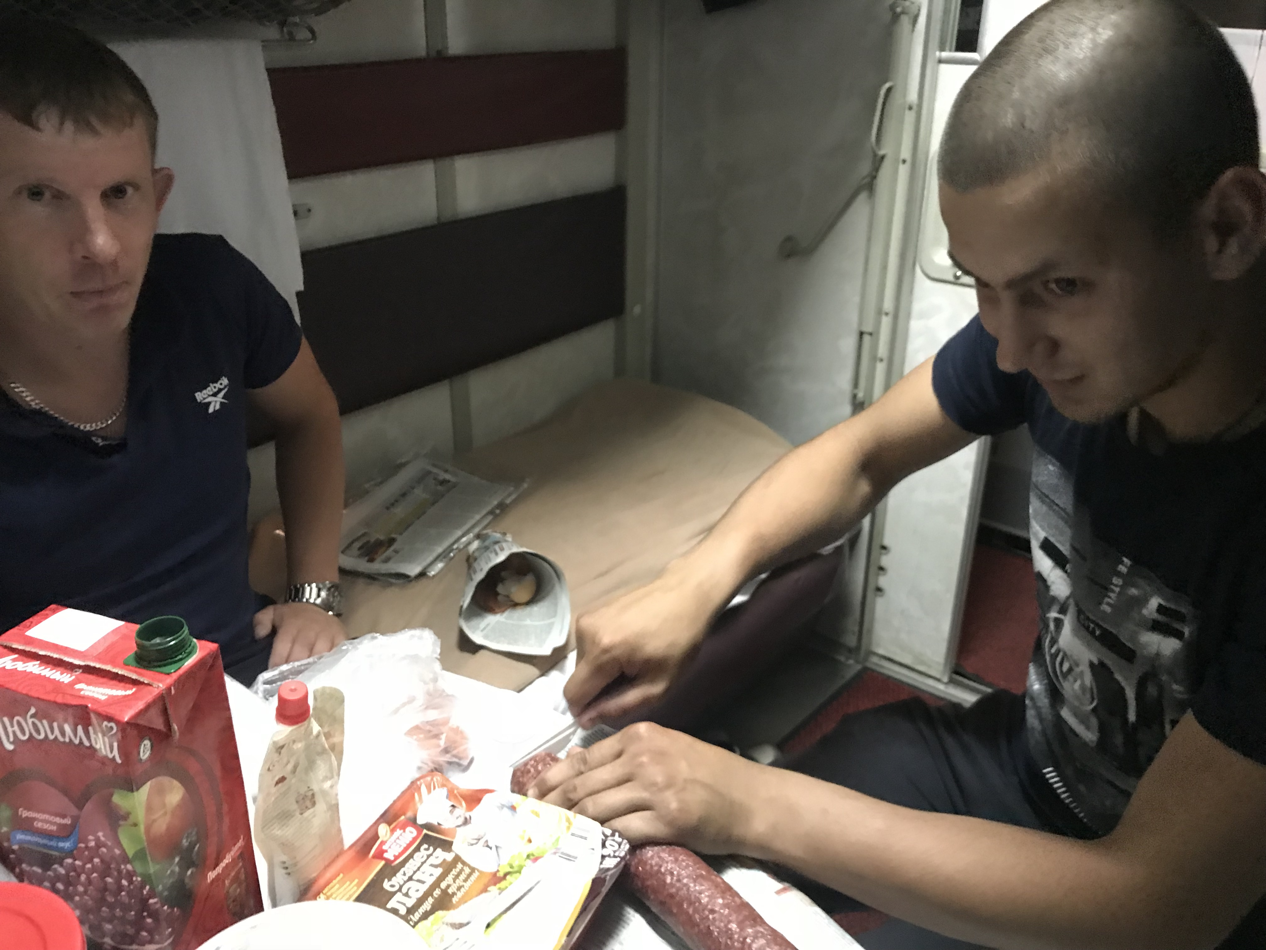 Russian cabin-mates sharing food from home, as customary.