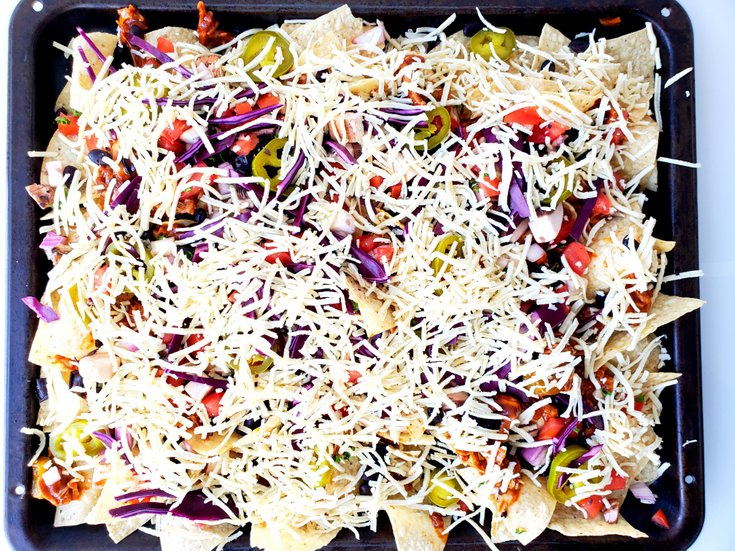 Nachos with vegetable toppings and vegan cheese