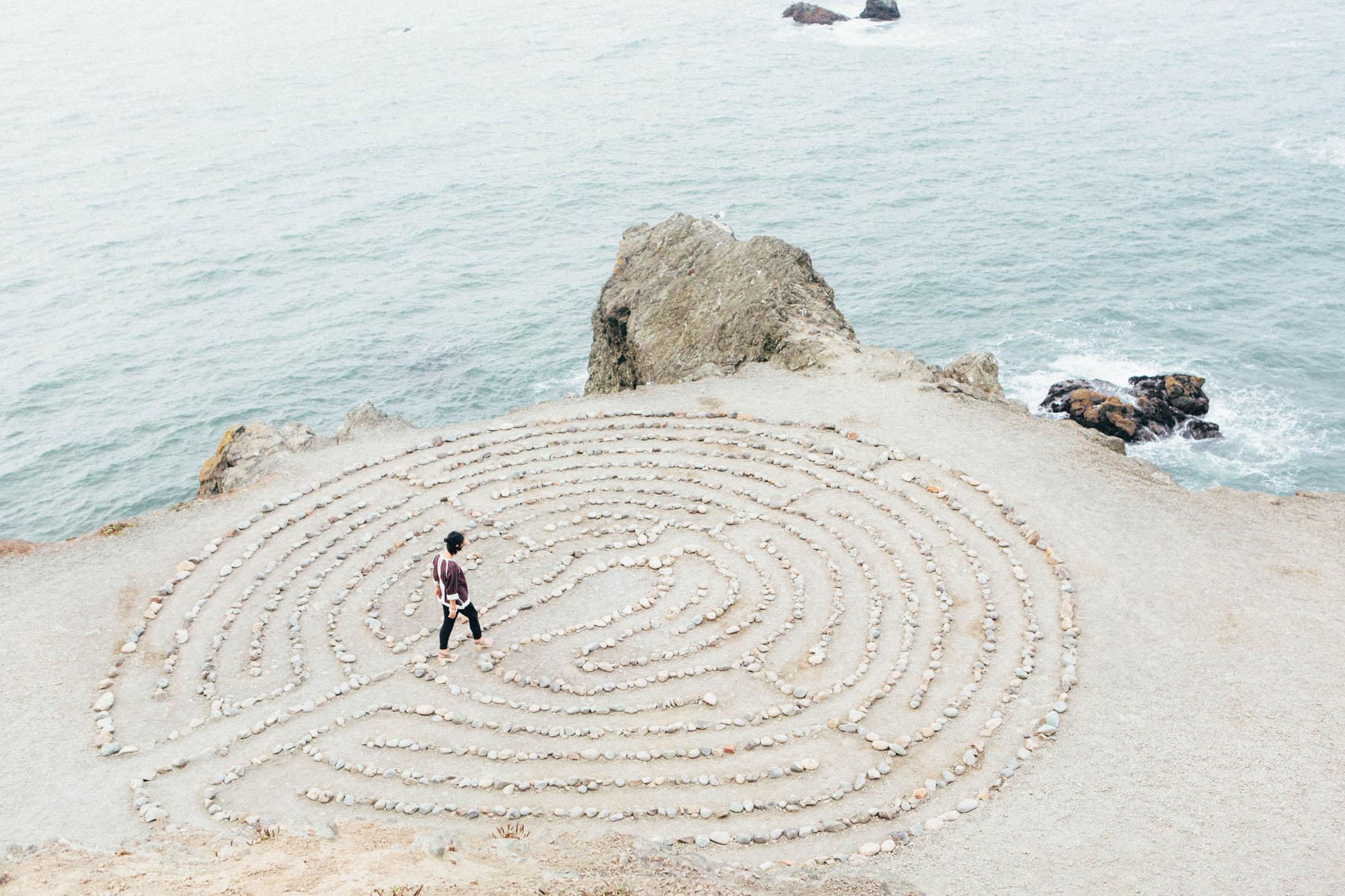 Woman near the ocean walking through a maze made of large rocks