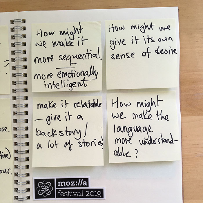 yellow sticky notes in a grid of four pasted into a notebook