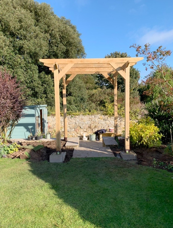 A small standalone pergola which a customer has built over some steps leading down to their driveway