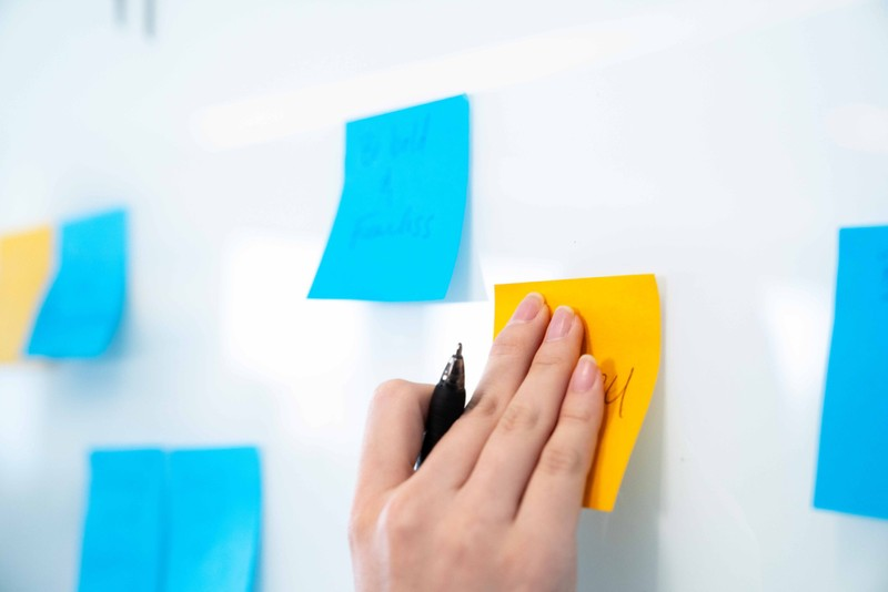 A hand holding a pen puts a sticky note on a whiteboard