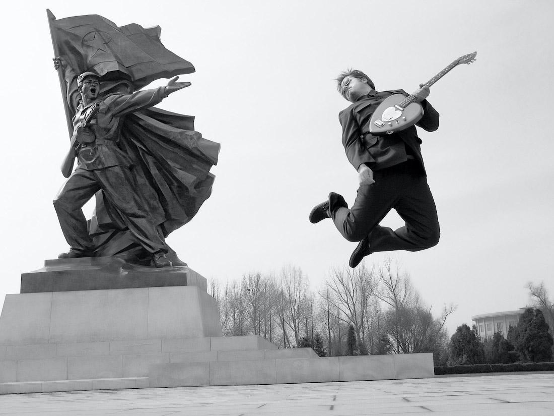 Мортен Тровик оттачивает рок-н-ролльный драйв нафоне Монумента победы вотечественной освободительной войне, Пхеньян. Фото изкниги «Предатель вСеверной Корее»