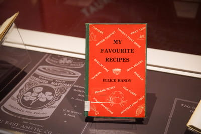 A close-up of a small book with a bright red cover. The book's title and author is My Favourite Recipes by Ellice Handy.