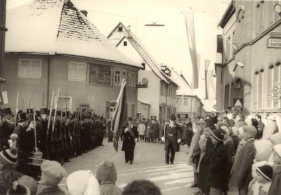 Hauptmann Edmund Väth und den Fähnrich Georg Behl beim Fahne holen. Wie an der Uhr der Sparkasse zu sehen ist, ist es gerade 10:30 Uhr, also nach der Kirche am Morgen. Links im Bild sind Joseph Brönner, Kasper Spiegel und Wilhelm Hoffmann zu sehen