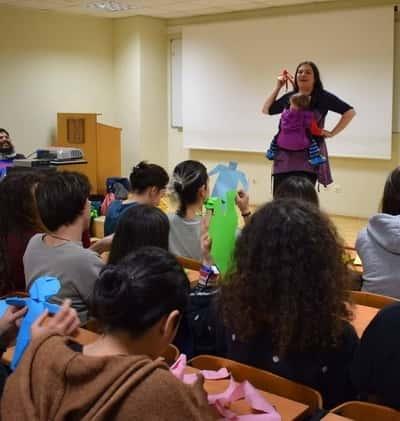 Η Αγγελική μιλάει σε μια τάξη παιδιά κρατώντας το παιδί της.