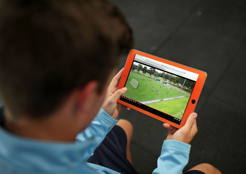 Soccer player watches gameplay on tablet