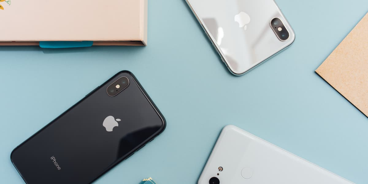 A collection of iPhones X's in assorted colors on a blue table