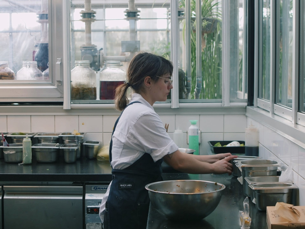 Table Sage Rate's Top Amsterdam Restaurants- De Kas female chef preparing sustainable, local food in kitchen