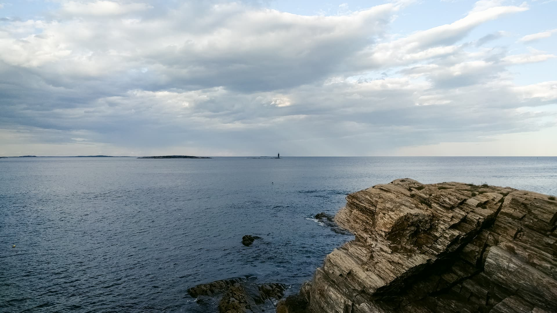 Looking out over the Atlantic Ocean from a rocky Maine beach. A lighthouse can barely be seen in the distance near the center of the frame; behind it, on the horizon, rain.