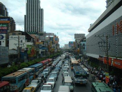 Ein kleines Verkehrsproblem.  Ich machte mich schon damit vertraut, auch diesen Bus niemals besteigen zu können, als wir dann um sechs doch noch einen Taxifahrer fanden, der uns zum Busbahnhof brachte. Leider ging sein Taxameter nicht und wir mussten uns auf 400 einigen. Mit Taximeter wäre es ein Viertel gewesen. Auf der Fahrt erzählte Yai dem Taxi-Thai, was wir am Morgen alles gegessen hatten, woraufhin er mir bewundernde Blicke in den Rückspiegel warf und den Preis halbierte. Wir kamen fünf vor Sieben auf dem Bahnhof an, fanden den Bus eine Minute vor Sieben und fuhren dreissig Minuten nach Sieben los. Verspätung. Klar.  Jedenfalls war ich im Bus der einzige Farang, also kam ich in den Genuss eines schlechten thailändisch synchronisierten japanischen Filmes gefolgt von einer Karaoke-VCD.   Es gibt übrigens nur 5 thailändische Popsongs, die jeder Interpret in einer neuen Version interpretiert. Meistens geht es in den Songs um Männer, die ihre Frauen für andere Frauen verlassen, dann plötzlich feststellen, dass die neue Frau bereits einen Mann hat, auf Knien zurückgekrochen kommen und das Haus leer vorfinden, weil die erste Frau ihrerseits nun den Mann verlassen hat. Sehr komplizierter Stoff.  Der ganze Bus sang mit.   Gegen sechs Uhr Morgens kamen wir zur Fähre, halb acht hatte meine Insel mich wieder, halb neun war ich zu Hause, um neun lag ich im Bett (ich kann in Bussen auf thailändischen Stra?en nicht schlafen, was eventuell an den vielen Schlaglöchern liegen könnte) und träumte von Taxirennen und schwabbeligem Rindfleisch. Arbeiten war ich an dem Tag auch noch.  Und nächste Woche muss ich wieder nach Krungthep. Diesmal allein. Dann werde ich mal ein paar Tempel ansehen. Wenn ich sie denn finde.  PS: Viel langweiliger Stoff für 14 Stunden Bangkok. Länger sollte man da aber auch nicht bleiben.