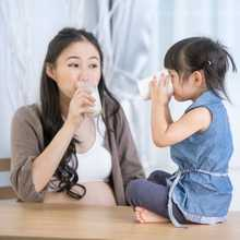 Happy asian family Mom and daughter drink milk at home .