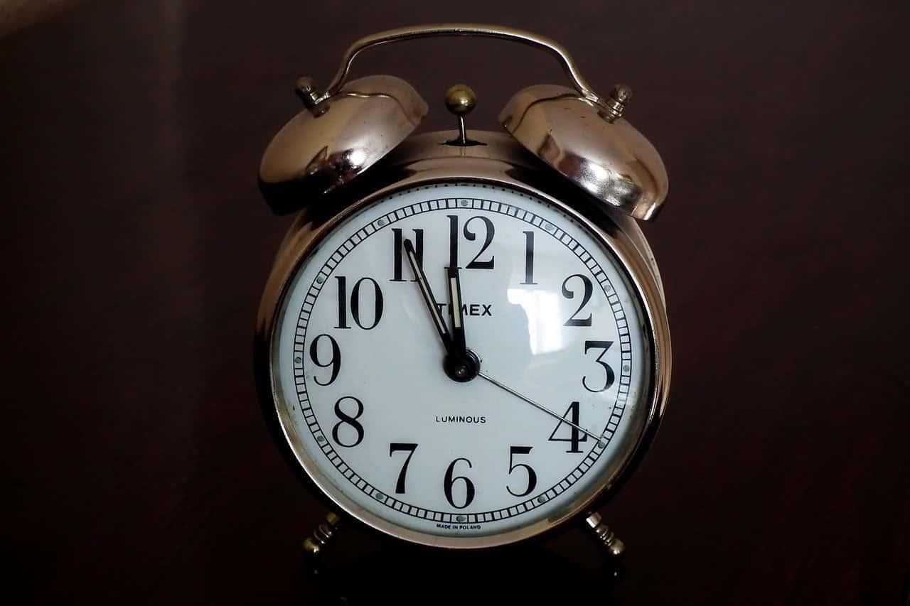 Old alarm clock nearing midnight on New Year's Eve