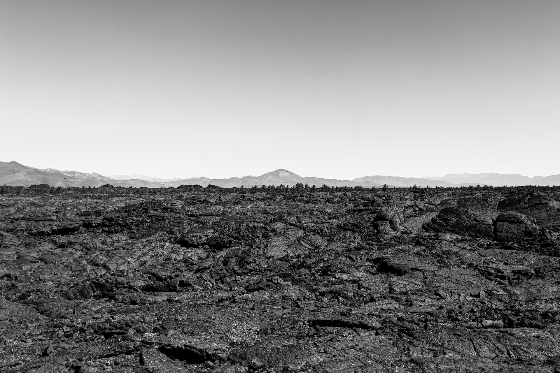 A field of pillowy lava flows  stretches towards the horizon. In the distance, a lava dome rises distinctly above the surrounding mountains.