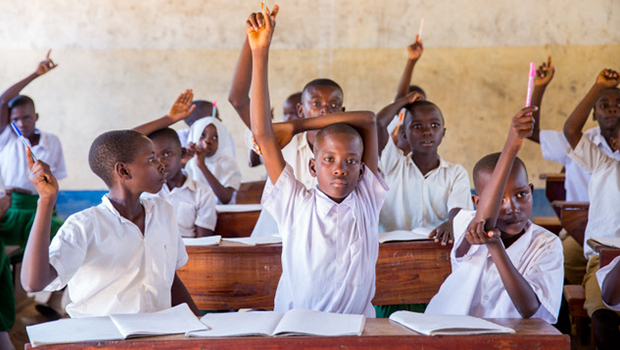 Children in a classroom raise their hands