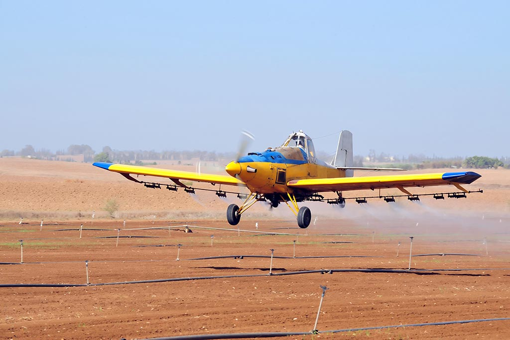 Agricultural aircraft are used for hydroseeding. Here an an agricultural aircraft, sometimes called a spray plane or crop duster, applies chemicals to a field of crops.