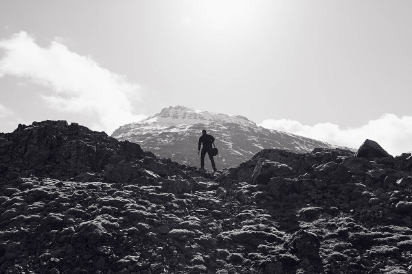 Man looking at a higher peak from a plateau