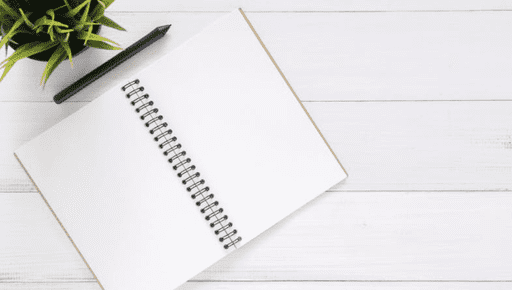 Blank notepad sits on white wooden desk with pens and plant for UK accountants #accountancy