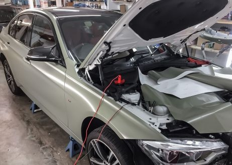 BMW 3 series car being vinyl wrapped in khaki green