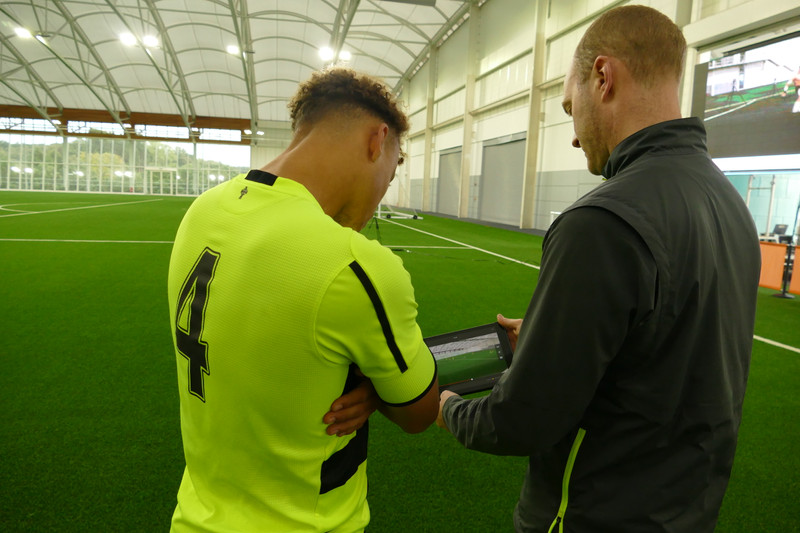Coach shows player video replays at soccer practice