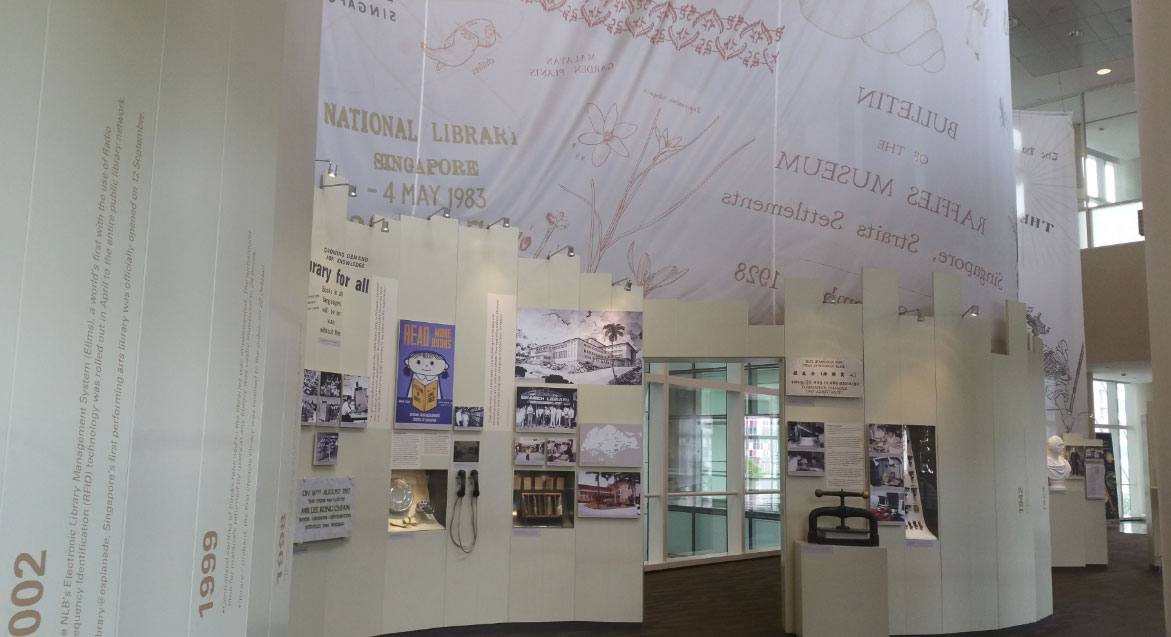 A photo of the side of the exhibition. Images and captions are on the walls. An old book-press machine is on a pedestal. On the following wall, there is a small TV screen with audio handsets.